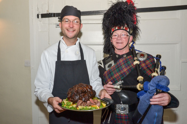 Chef holding venison joint on silver tray and piper holding bag pipes.